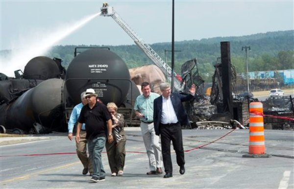 El primer ministro de Canadá, Stephen Harper, saluda a personas durante su visita a la comunidad de Lac-Megantic, en Quebec, el domingo 7 de julio de 2013. El sábado, un tren con vagones que transportaban petróleo crudo se descarriló el sábado; el incendio y explosiones subsiguientes destruyeron el distrito comercial de la localidad. (AP Foto/The Canadian Press, Paul Chiasson)