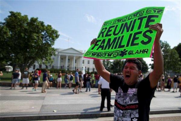 Carlos Guzman, de Albany, sostiene un cartel sobre la reunificación de la familia durante una manifestación frente a la Casa Blanca en Washington, el miércoles 24 de julio de 2013. Docenas de personas se concentraron en el lugar para solicitar al presidente Barack Obama que suspenda inmediatamente las deportaciones de inmigrantes sin papeles. (AP Photo/Evan Vucci)