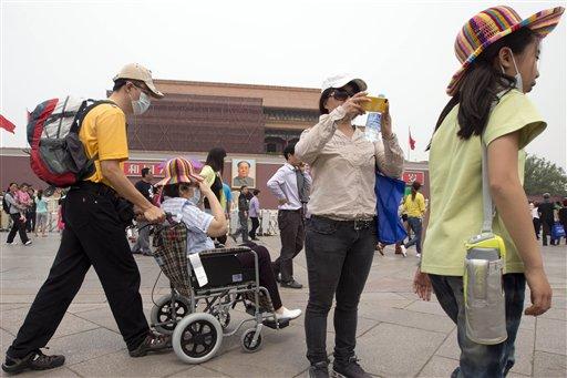 Visitantes de la plaza Tiananmen se protegen con un cubrebocas de la fuerte contaminación en Beijing, el 7 de mayo de 2013. Un estudio dado a conocer el 9 de julio de 2013 vincula la densa contaminación ambiental por la quema de carbón con una menor esperanza de vida en el norte de China. (Foto AP/Ng Han Guan)