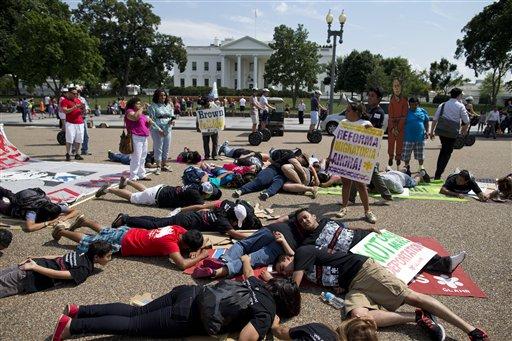 Manifestantes yacen sobre el piso frente a la Casa Blanca en Washington, el miércoles 24 de julio de 2014. Docenas de personas se concentraron en el lugar para solicitar al presidente Barack Obama que suspenda inmediatamente las deportaciones de inmigrantes sin papeles. (AP Photo/Evan Vucci)
