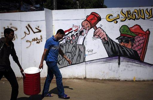 """Partidarios del presidente egipcio depuesto Mohamed Morsi caminan junto a una pared pintada con grafito que dice en árabe """"no al golpe"""" el jueves 25 de julio de 2013. El jueves el líder de la Hermandad Musulmana atacó con inusual dureza al jefe del ejército egipcio al decir que la deposición del presidente Mohamed Morsi era un crimen peor que destruir la Kaaba, el lugar más sagrado del islam. (Foto AP/Khalil Hamra)"""