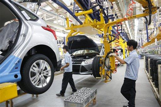 En esta fotografía del lunes 27 de agosto de 2012 proporcionada por Ford Motor Co., un par de trabajadores ensamblan un automóvil en la nueva planta Ford/CFMA Chongqing tras su inauguración en Chongqing, China. (Foto AP/Ford Motor Co.)