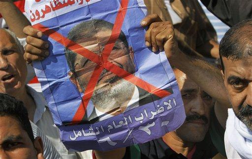 Manifestantes egipcios lanzan consignas contra el presidente Mohammed Morsi durante una protesta en la plaza Tahrir, punto central de los disturbios en El Cairo, Egipto, el viernes 21 de junio de 2013. La Comisión Presidencial de Elecciones investigará las quejas del ex candidato presidencial Ahmed Shafiq quien afirma que ocurrieron irregularidades y falsificaciones en las elecciones del año pasado que él perdió por muy estrecho margen ante Morsi. (Foto AP/ Amr Nabil)