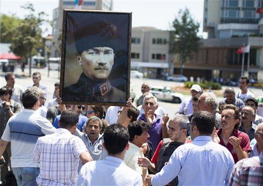 Un hombre sostiene un cartel con una imagen de Mustafa Kemal Ataturk a la espera de entrar al parque Gezi en la plaza Taksim en Estambul, Turquía, el lunes 8 de julio de 2013. El gobierno había anunciado que abriría el parque pero lo cerró poco después cuando los manifestantes empezaron a dirigirse hacia la zona para realizar un mítin. (Foto AP/Gero Breloer)