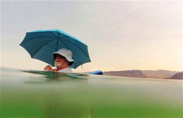 Mike Bouse, residente  de Henderson, Nevada, se protege del sol con una sombrilla mientrass flota en las aguas de Boulder Beach en el lago Mead, el sábado 29 de junio del 2013 en Nevada. Una intensa ola de calor continuará por el área desértica del oeste de Estados Unidos por los estados de California, Nevada y Arizona. Se calcula que la temperatura ascenderá hasta los 50 grados centíngrados (120Fº).  (Foto AP/Julie Jacobson)