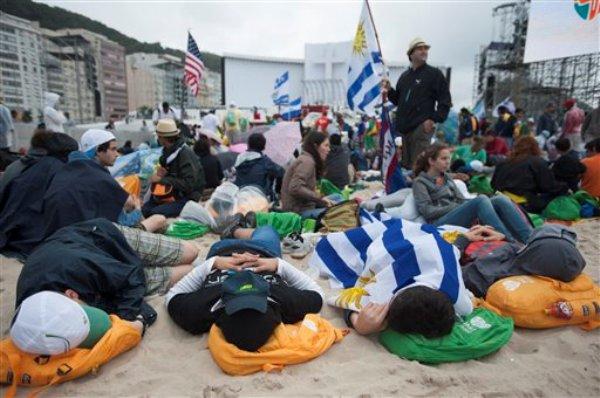 Peregrinos duermen en la playa de Copacabana pocas horas antes de que la Iglesia inaugure la Jornada Mundial de la Juventud, evento en el que se espera la participación de cientos de miles de fieles procedentes de varios países de América Latina. Rio de Janeiro, martes 23 de julio de 2013. (AP foto/Nicolas Tanner)
