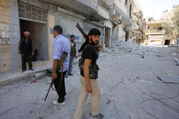 Free Syrian Army fighters walk in the Salah El Dine neighbourhood of Syria's northwest city of Aleppo