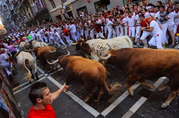 Juerguistas huyen de un toro en una de las corridas por el festival de San Fermín, en Pamplona, España, el domingo 7 de julio de 2013. (Foto AP/Alvaro Barrientos)