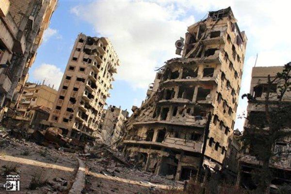 Numerosos edificios están destruidos debido a los ataques del gobierno sirio contra el vecindario de Jouret al-Chiyah en Homs, Siria, el miércoles 3 de julio de 2013. Unos 2.500 civiles están atrapados en Homs, donde el ejército pretende expulsar a los rebeldes. (AP Foto/Lens Young Homsi)
