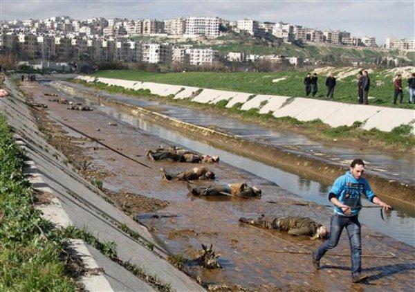 """ARCHIVO - En imagen del martes 29 de enero de 2013, un hombre pasa al lado de cadáveres en los márgenes de un río man en el vecindario de Bustan al-Qasr en Aleppo, Siria. Las reuniones entre el gobierno de Siria y una delegación de Naciones Unidas asignada a la investigación de acusaciones por el uso de armas químicas en la guerra civil del país """"resultaron en un acuerdo que permite seguir adelante"""", reportaron el sábado 27 de julio medios oficiales sirios. (Foto AP/Abdullah al-Yassin)"""