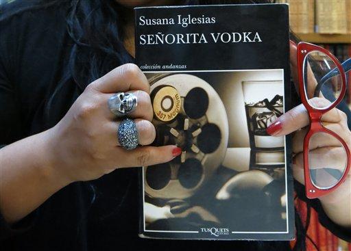 """La escritora mexicana Susana Iglesias sostiene su libro """"Señorita Vodka"""" durante una entrevista en la Ciudad de México el martes 16 de julio del 2013. Iglesias dice que su novela es un homenaje a las bailarinas exóticas. (AP Foto/Isaac Garrido)"""