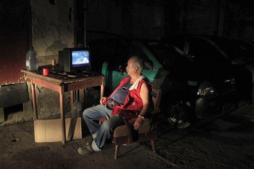 Andrés Ortega mira el 30 de junio del 2013 en La Habana un juego entre Bravos y Nacionales, el primer encuentro de las grandes ligas estadounidenses que se transmite en Cuba en más de medio siglo. (AP Photo/Franklin Reyes)