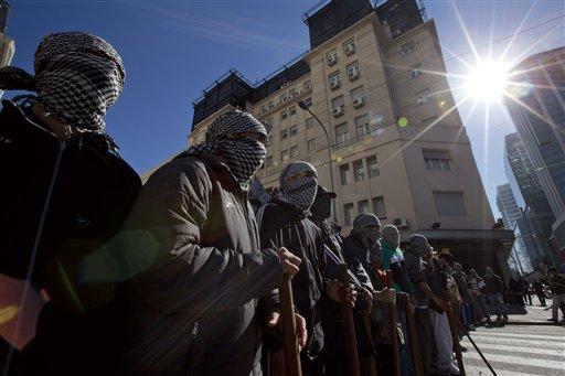 Manifestantes encapuchados marchan durante una protesta contra un acuerdo entre el ente estatal YPF argentino y la petrolera estadounidense Chevron en las afueras de las oficinas centrales de YPF en Buenos Aires, Argentina, el martes 16 de julio de 2013. (AP Photo/Victor R. Caivano)