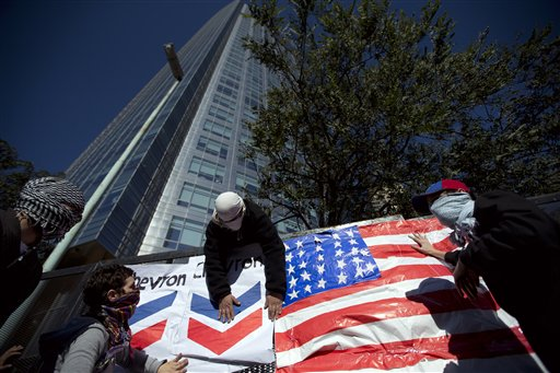 Manifestantes colocan el logotipo de la petrolera Chevron sobre una bandera de Estados Unidos durante una protesta contra un acuerdo entre el ente estatal YPF argentino y la petrolera estadounidense en las afueras de las oficinas centrales de YPF en Buenos Aires, Argentina, el martes 16 de julio de 2013. (AP Photo/Victor R. Caivano)