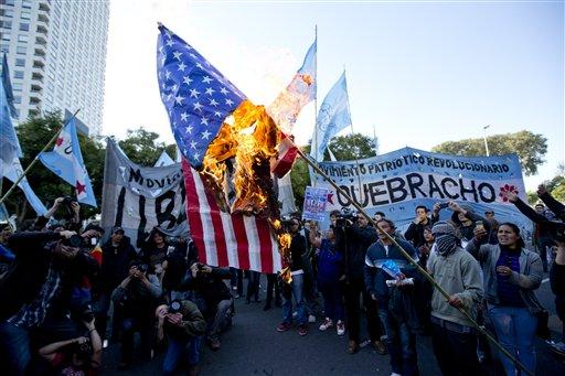 Manifestantes queman una bandera de Estados Unidos durante una protesta contra un acuerdo entre el ente estatal YPF argentino y la petrolera estadounidense Chevron en las afueras de las oficinas centrales de YPF en Buenos Aires, Argentina, el martes 16 de julio de 2013. (AP Photo/Victor R. Caivano)