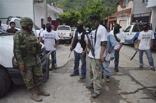 Un soldado del ejército mexicano habla con hombres armados de un grupo de autodefensa en el poblado de Aquila, Michoacán, el miércoles 24 de julio de 2013.