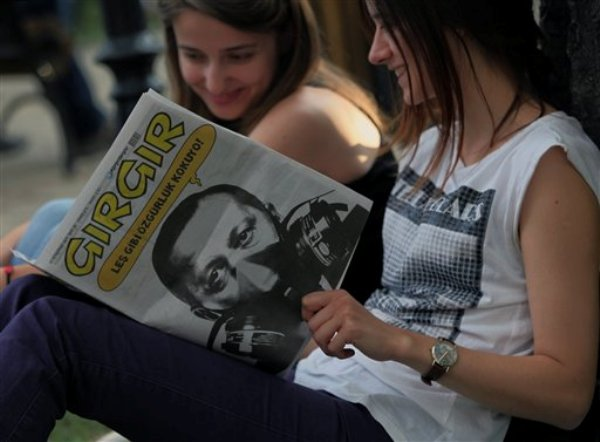 Jóvenes turcas leen Girgir, una popular revista satírica que tiene en su portada al primer ministro turco Recep Tayyip Erdogan, en el parque Kugulu de la capital Ankara, el lunes 10 de junio de 2013. Manifestantes contra el gobierno y policías se enfrentan por segunda semana. (Foto AP/Burhan Ozbilici)