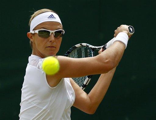 La belga Kirsten Flipkens realiza una devolución a la italiana Flavia Pennetta durante un encuentro en Wimbledon, el lunes 1 de julio de 2013. Durante ese encuentro, Flipkens pidió que un periodista de la BBC guardara silencio (AP Foto/Sang Tan)