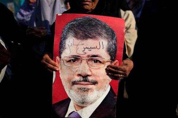 """Una simpatizante sostiene un cartel con la foto del presidente islamista de Egipto Mohamed Morsi, en el que se lee """"Sisi traidor"""", durante una manifestación en Ciudad Nasser, en El Cairo, Egipto, el jueves 4 de julio de 2013. El presidente del Tribunal Constitucional Supremo de Egipto asumió el jueves el cargo de presidente interino del país, luego que el ejército depuso a Morsi y lanzó una persecución contra la Hermandad Musulmana, el grupo al que Morsi pertenece. (AP Foto/Hassan Ammar)"""