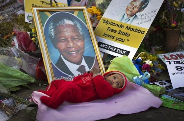 Oamohetswe Mabitsela, de cuatro meses, es colocado por su madre junto a una imagen de Nelson Mandela para tomarle una fotografía con la cámara de su teléfono afuera del hospital donde el ex presidente se encuentra hospitalizado en Pretoria, Sudáfrica, el jueves 4 de julio de 2013. Mandela continúa en estado crítico pero estable y no está en estado vegetativo, informaron el viernes 5 de julio las autoridades de Sudáfrica. (Foto AP/Ben Curtis)