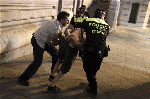 Policías arrestan a un manifestante durante una protesta contra el gobierno frente a las oficinas centrales del Partido Popular, el jueves 18 de julio de 2013, en Madrid, España. (Foto AP/Andrés Kudacki)