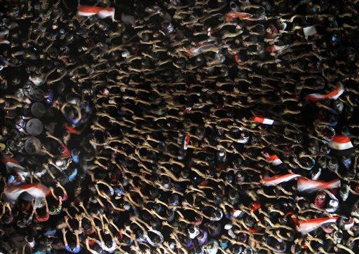Manifestantes egipcios alzan sus manos y sostienen banderas nacionales durante las protestas en contra del presidente Mohammed Morsi en la Plaza Tahrir, el punto neurálgico de las revueltas en El Cairo, Egipto, el viernes 28 de junio de 2013. Se espera que miles de detractores y partidarios de Morsi participen en las marchas multitudinarias del sábado luego de una violenta serie de enfrentamientos entre ambos bandos que ha dejado al menos siete muertos. (Foto AP/Amr Nabil)