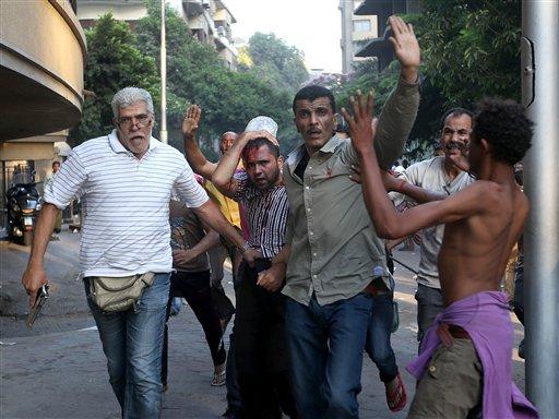 Opositores del derrocado presidente egipcio Mohamed Morsi detienen a un presunto partidario del ex mandatario que resultó herido en enfrentamientos en El Cairo, Egipto, el lunes 22 de julio de 2013. (Foto AP/Hussein Malla)