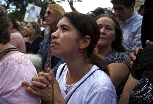 Peregrinos rezan cuando el papa Francisco bendice a la multitud durante el Angelus en el Palacio Sao Joaquim, residencia del arzobispo de Rio en Rio de Janeiro, el viernes 26 de julio de 2013. (AP Photo/Jorge Saenz)