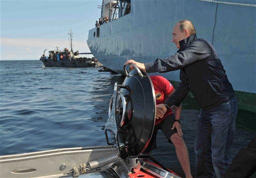El presidente ruso Vladimir Putin sostiene la escotilla del submarino tras sumergirse en el Sea Explorer 5 cerca de la isla de Gogland, 180 kilómetros al oeste de San Petersburg, Rusia, el lunes 15 de julio de 2013. (Foto AP/RIA-Novosti, Alexei Nikolsky, Servicio Presidencial de Prensa)