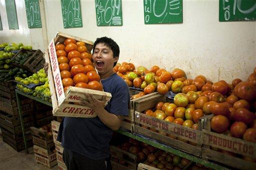 ARCHIVO - En esta foto de archivo del 4 de febrero de 2013, un empleado de verduleríua cambia bromas con otros, fuera de la foto, mientras carga un cajón de tomates en Buenos Aires. El gobierno pidió a los consumidores el viernes 12 de julio de 2013 que disminuyan el consumo de tomates durante los próximos dos meses. (AP Foto/Victor R. Caivano, File)