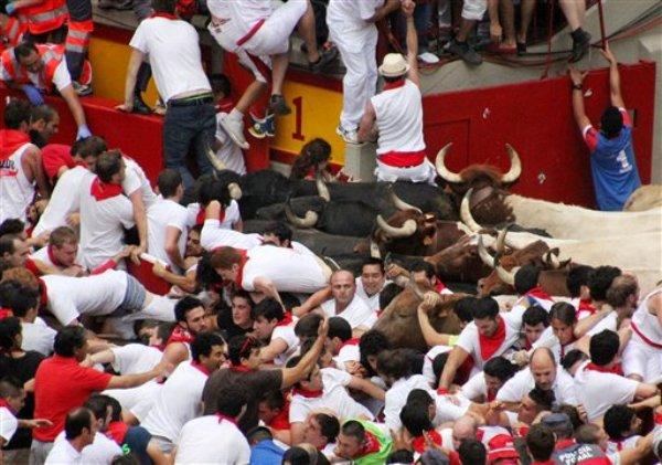 Corredores tropiezan y caen frente a los toros y bloquean la entrada a la plaza durante el encierro del festival de San Fermín del sábado 13 de julio de 2013 en Pamplona, España. (Foto AP/Joseba Etxeberria)