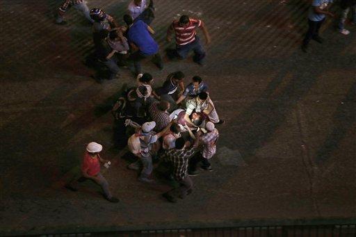 Personas transportan a dos lesionados durante enfrentamientos entre partidarios y oponentes del depuesto mandatario islamista de Egipto, Mohammed Morsi, que estallaron en El Cairo, Egipto, el viernes 5 de julio de 2013. (AP Foto/Hassan Ammar)