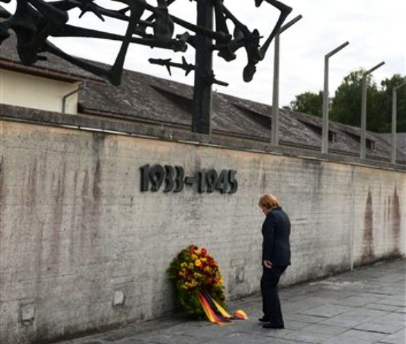 La canciller alemana Angela Merkel participa en una ceremonia para dejar una ofrenda durante su visita al campo de concentración de Dachau, donde más de 43.000 personas fueron asesinadas durante el régimen nazi de 1933 a 1945 en Dachau, en el sur de Alemania, el martes 20 de agosto de 2013. (Foto AP/Kerstin Joensson)