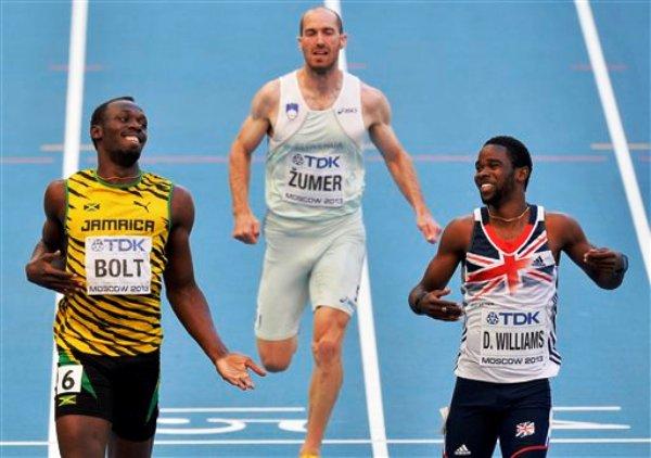El jamaiquino Usain Bolt, izquierda, y el británico Delano Williams, extremo derecho, reaccionan tras competir en las eliminatorias de los 200 metros del Mundial de atletismo el viernes 16 de agosto de 2013. (AP Foto/Martin Meissner)