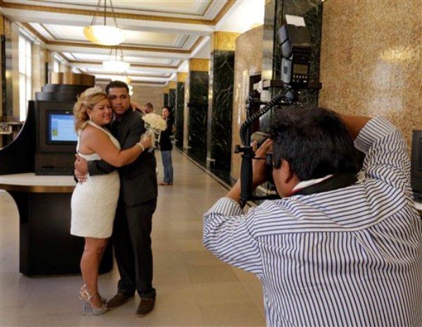 Braulio Cuenca fotografía a Jorge Mejía e Irma Aguilar en el registro civil de Nueva York el 7 de agosto del 2013. Cuenca es un ecuatoriano que lleva 20 años fotografiando bodas en Nueva York y a menudo sale de testigo. (AP Photo/Richard Drew)