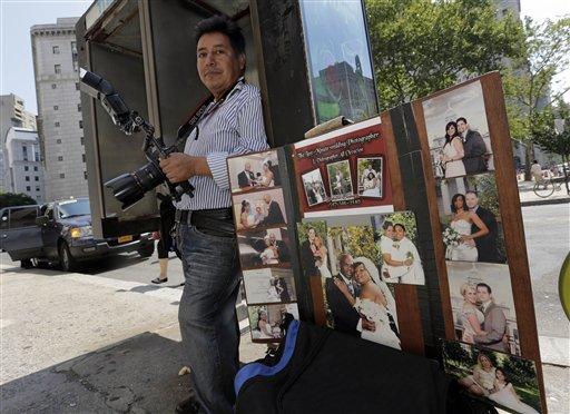 Braulio Cuenca espera frente al registro civil de Nueva York que aparezca alguna pareja que quiera fotos de su casamiento el 7 de agosto del 2013. Cuenca es un ecuatoriano que lleva 20 años fotografiando bodas en Nueva York y a menudo sale de testigo. (AP Photo/Richard Drew)