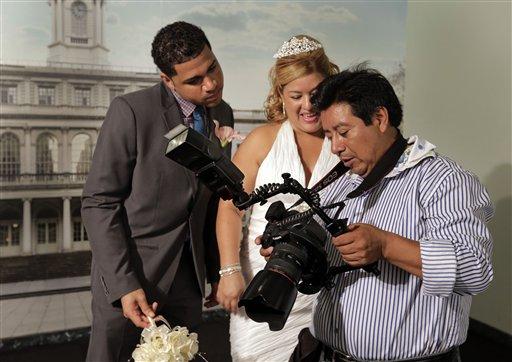 Braulio Cuenca le muestra a Jorge Mejía e Irma Aguilar las fotos que tomó de su boda en el registro civil de Nueva York el 7 de agosto del 2013. Cuenca es un ecuatoriano que lleva 20 años fotografiando bodas en Nueva York y a menudo sale de testigo. (AP Photo/Richard Drew)