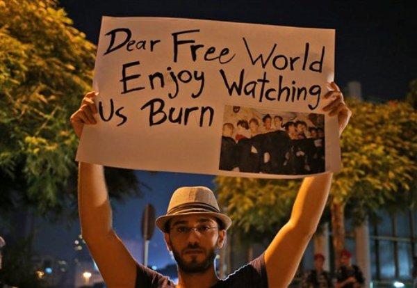 Un sirio que vive en Beirut sostiene un cartel durante una vigilia contra el supuesto ataque con armas químicas ocurrido en Damasco, frente a las oficinas de la ONU en la capital de Líbano, el miércoles 21 de agosto de 2013. (Foto AP/Hussein Malla)