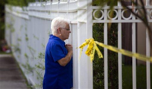 Una mujer no identificada se asoma desde la reja de una casa donde hubo un asesinato, en Miami, el jueves 8 de agosto de 2013. Según las autoridades, Derek Medina mató a tiros a su esposa y al parecer publicó la foto del cadáver en Facebook. (Foto AP/J Pat Carter)