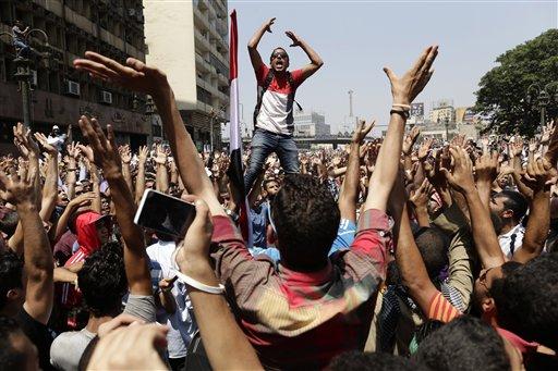 Simpatizantes del depuesto presidente de Egipto, Mohammed Morsi, corean lemas contra el ministro de defensa egipcio, el general Abdel-Fattah el-Sissi antes de los enfrentamientos con las fuerzas de seguridad en la Plaza Ramses, en el centgro de El Cairo, la capital egipcia el viernes 16 de agosto del  2013. Varias empresas internacionales que operan en Egipto suspendieron sus operaciones durante los tres días de violentos disturbios callejeros que crearon una situación de inseguridad pública en El Cairo.  (Foto AP/Hassan Ammar)