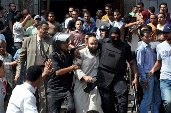 Fuerzas de seguridad egipcias escoltan a un partidario de la Hermandad Musulmana mientras abandonan la mezquita al-Fatah en la que cientos de manifestantes islamismas se encerraron durante toda la noche tras un día de violentos enfrentamientos callejeros que dejaron muchos muertos, cerca de la explanada Ramsés en el centro de El Cairo, Egipto, el sábado 17 de agosto de 2013. (Foto AP/Hussein Tallal)