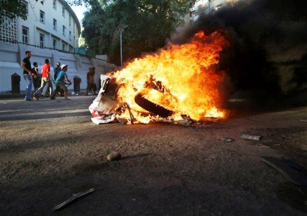 Opositores del derrocado presidente Mohamed Morsi pasan junto a una motoneta en llamas, incendiada durante enfrentamientos con partidarios de Morsi, en El Cairo, Egipto, el lunes 22 de julio de 2013. (Foto AP/Hussein Malla)