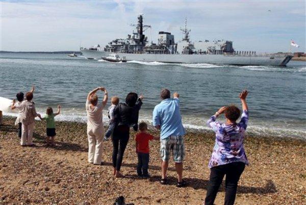 Personas saludan al barco HMS Westminster, de la armada real de Bran Bretaña, que parte de Potsmouth, Inglaterra, a Gibraltar, el martes 13 de agosto de 2013. La nave participará en maniobras en el mar Mediterráneo. (AP Foto/ Steve Parsons/PA)