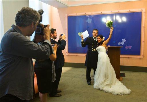 Goran Veljic (izq) fotografía a los recién casados Lisardo Hernández y Alnair Vivanco en el registro civil de Nueva York el 7 de agosto del 2013. Veljic, quien es de Serbia, y el ecuatoriano Braulio Cuenca son los dos únicos fotógrafos fijos que sacan fotos de bodas en ese registro civil. (AP Photo/Richard Drew)