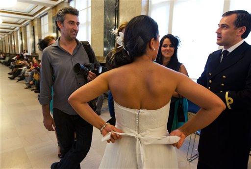 Goran Veljic (izq) conversa con Lisardo Hernández y Alnair Vivanco sobre las fotos que tomará de su boda en el registro civil de Nueva York el 7 de agosto del 2013. Veljic, quien es de Serbia, y el ecuatoriano Braulio Cuenca son los dos únicos fotógrafos fijos que sacan fotos de bodas en ese registro civil. (AP Photo/Richard Drew)