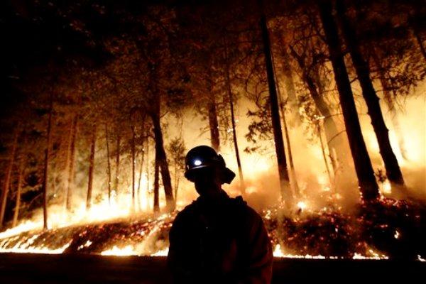 Un bombero observa un incendio mientras se establece una barrera contra fuego cerca del Parque Nacional Yosemite, California, el domingo 25 de agosto de 2013. (Foto AP/Jae C. Hong)