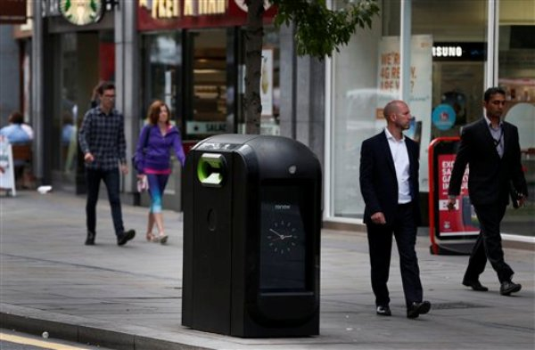 Los peatones pasan junto a un recipiente de basura en el centro de Londres el 12 de agosto del 2013. Las autoridades municipales intimaron a la firma Renew a poner fin inmediatamente a un programa que utiliza su red de recipientes, como este, para rastrear por medio de una red de Wi-Fi el paso de los portadores de teléfonos multiuso por el lugar (AP Foto/Lefteris Pitarakis)