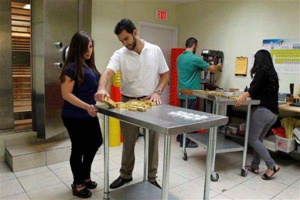 Jenna Kaloti Ramírez, izquierda,y su esposo Jorge Ramírez, centro, analizan barras de oro antes de colocarlos dentro de la caja fuerte de la casa de comercio Kaloti Metals & Logistics, el martes 25 de junio de 2013. (Foto AP/The Miami Herald, Carl Juste)
