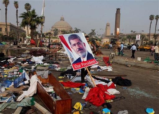 Un cartel con la imagen del ex presidente egipcio Mohammed Morsi está entre los escombros que quedaron tras el desalojo de un campamento en la plaza Nahda, en El Cairo, el jueves 15 de agosto de 2013. (Foto AP/Amr Nabil)