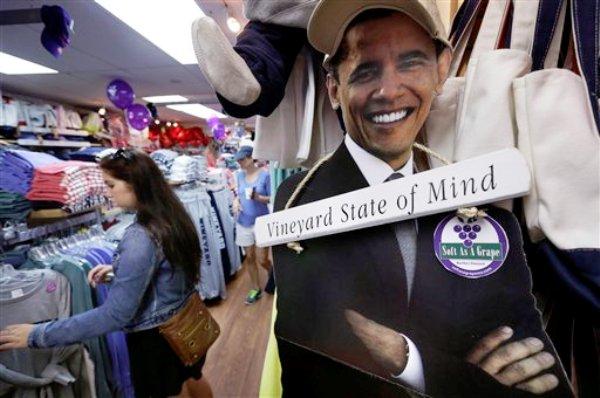 Meghan Ford ve un anaquel con ropa cerca de una fotografía del presidente Barack Obama, en una tienda de la isla Martha's Vineyard, el viernes 9 de agosto de 2013. Los Obama pasarán nueve días de vacaciones en la exclusiva isla de Massachusetts. (Foto AP/Steven Senne)